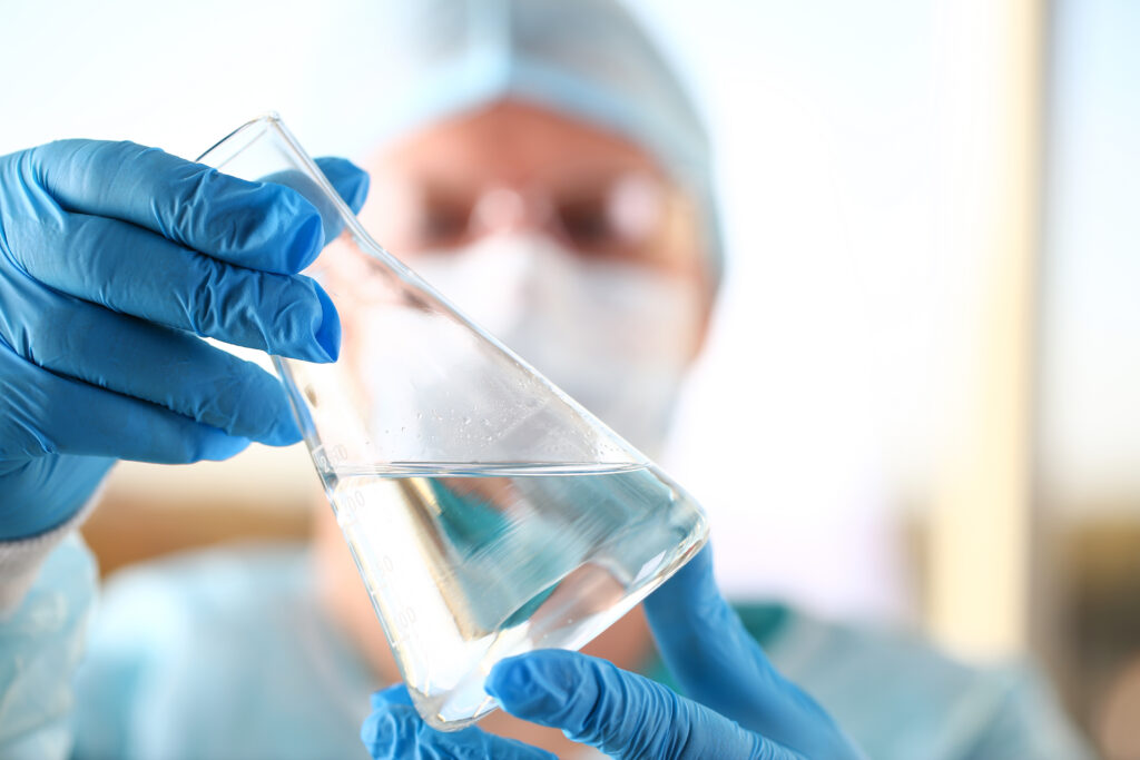 Man holding a vial of water for pharmaceutical water testing